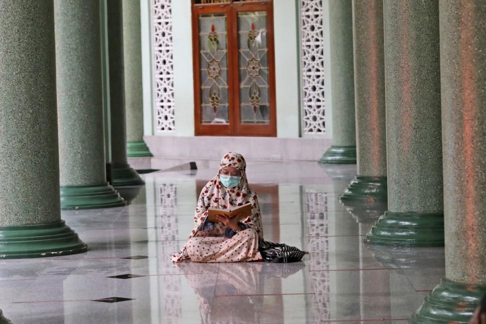 Ramadan: In einer Moschee in Jakarta, Indonesien, liest eine Gläubige im Koran, während sie auf den ersten Sonnenuntergang im Ramadan wartet. Sobald es dunkel ist, wird sie ihr Fasten unterbrechen.