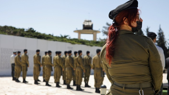 Israeli soldiers take part in a ceremony marking Israel's Memorial Day at a memorial site for fallen soldiers from the Armored Corps in Latrun