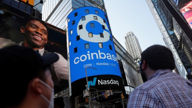 People watch as the logo for Coinbase Global Inc, the biggest U.S. cryptocurrency exchange, is displayed on the Nasdaq MarketSite jumbotron at Times Square in New York