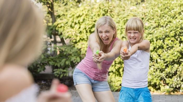 Mother and two girls splashing with water guns in garden model released Symbolfoto PUBLICATIONxINxGERxSUIxAUTxHUNxONLY