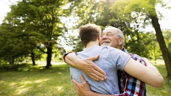 Happy senior father hugging his adult son in a park model released Symbolfoto PUBLICATIONxINxGERxSUIxAUTxHUNxONLY HAPF0