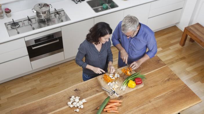 Mature couple preparing vegetables in kitchen model released Symbolfoto property released PUBLICATIO