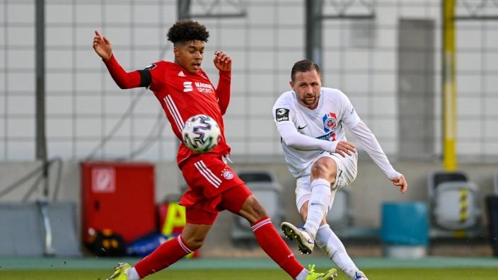 v.li.: Justin Ishia Che (Bayern München, FCB, 35) John Verhoek (Rostock, 18) erzielt dqas Tor zum 0:1, Zweikampf, Duell,