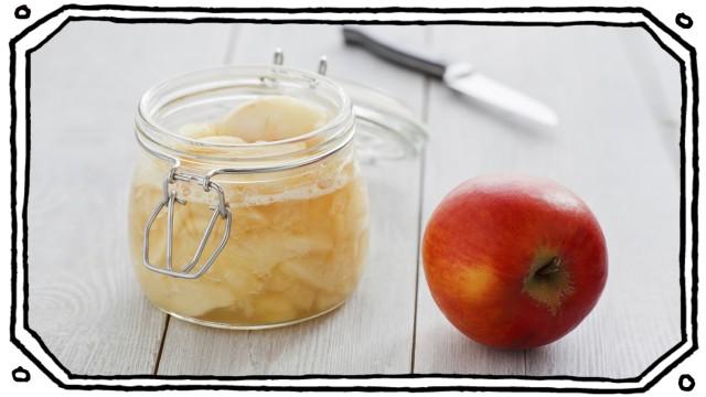 Frischer Apfelkompott im Glas mit einem Apfel auf einem Holzuntergrund.