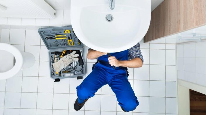 High Angle View Of Male Plumber Repairing A Sink In Bathroom model released Symbolfoto PUBLICATIONxI