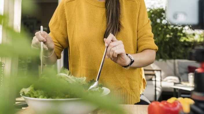 Smiling young woman filming with smart phone while preparing food at home model released Symbolfoto property released UU