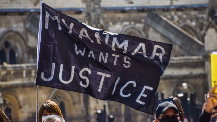 April 24, 2021, London, United Kingdom: A protester holding a flag saying Myanmar Wants Justice in Parliament Square du