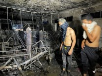 People look on at Ibn Khatib hospital after a fire caused by an oxygen tank explosion in Baghdad