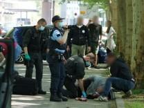 Die Polizei betreut einen Mann, der in Stuttgart gegen Corona-Auflagen demonstrieren wollte und zusammengeschlagen wurde.