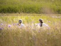 Abstand halten. Zwei Schuelerinnen sitzen im Abstand in Zeiten von Corona in einer bluehenden Wiese. Bonn Deutschland **
