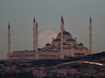 The full moon, also known as the Supermoon, rises behind the Camlica Mosque in Istanbul