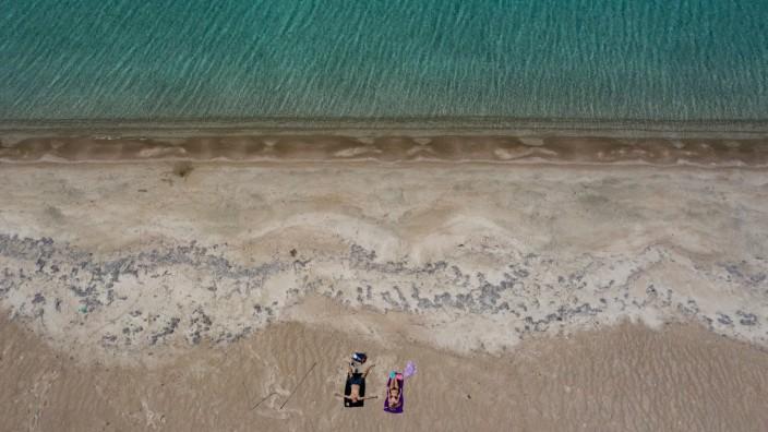 Corona-Krise: Sonnenbad am Strand der griechischen Insel Elafinisos. Für die meisten Griechen gelten aber starke Einschränkungen ihrer Bewegungsfreiheit.