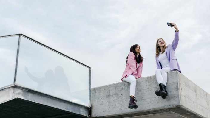 Sisters taking selfie through smart phone while sitting on rooftop in city against sky model released Symbolfoto TCEF013