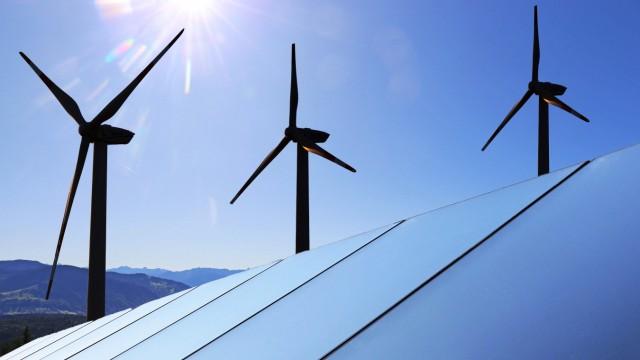 Symbolbild Energiewende: Solardach mit Windkraftanlagen im Hintergrund (Composing) *** Symbolic image Energy revolution