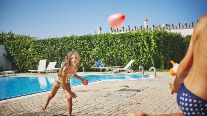 Girl and boy having a water fight with water gun and water bombs at the poolside model released Symb