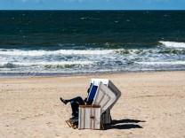 Ein Mensch sitzt auf Sylt am Strand in einem Strandkorb.
