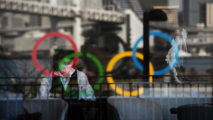 Die Olympischen Ringe spiegeln sich in der Scheibe eines Restaurants in Tokio. Trotz des Notstands sagt die Regierung, an den Plänen für Olympia ändere sich nichts.