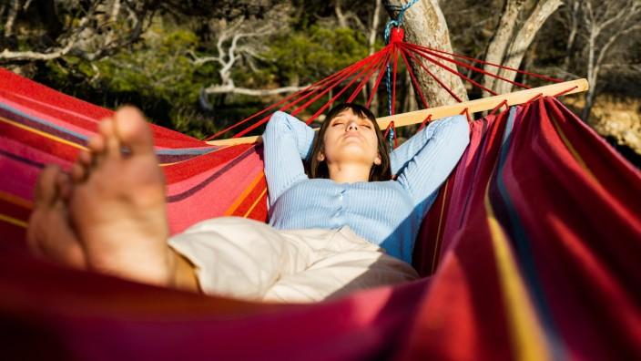 young woman caucasian sleeping in hammock Sant Elm, IB, Spain PUBLICATIONxINxGERxSUIxAUTxONLY CR_PESU210416-706701-01 ,m