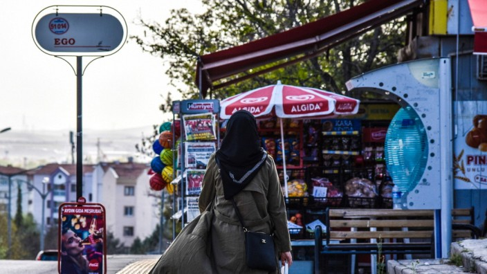 April 29, 2021, Ankara, Turkey: A woman holding shopping bags walks past a a small market before the start of a full lo
