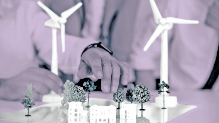 Close up of business people wind turbine model and houses on conference table model released Symbolf