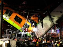 Rescuers work at a site where an overpass for a metro partially collapsed with train cars on it at Olivos station in Mexico City