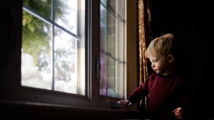 A little boy tries to open a window. Garden City South, New York, USA. PUBLICATIONxINxGERxSUIxAUTxONLY CR_FRRU191112-229