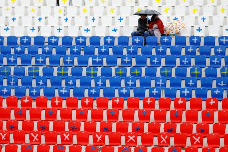 A couple sit under an umbrella amidst empty stadium seats during a football match in Stavropol