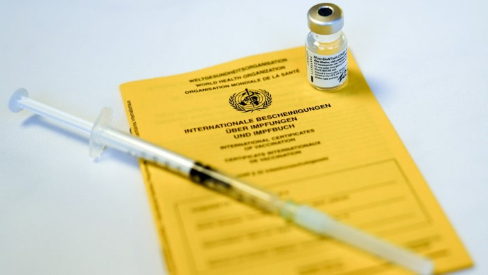 Impfstart in Koeln erste Bewohner von Pflegeheimen werden geimpft Symbolbild, Symbolfoto Impfpass mit einer Ampulle von