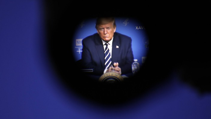 President Donald Trump, seen through a video camera s eyepiece, attends a coronavirus roundtable briefing at the Nation