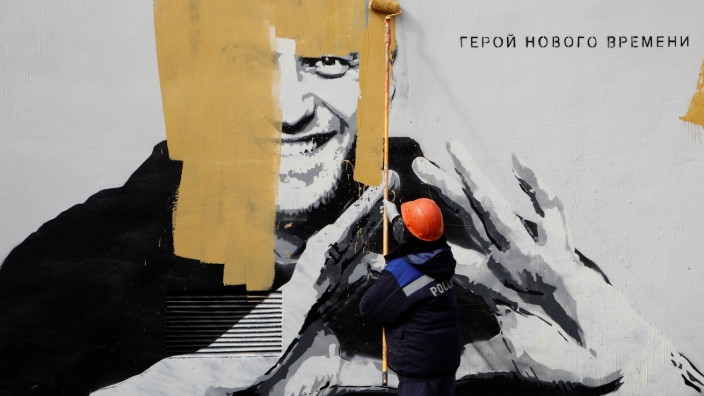A worker paints over a graffiti depicting Alexei Navalny in Saint Petersburg