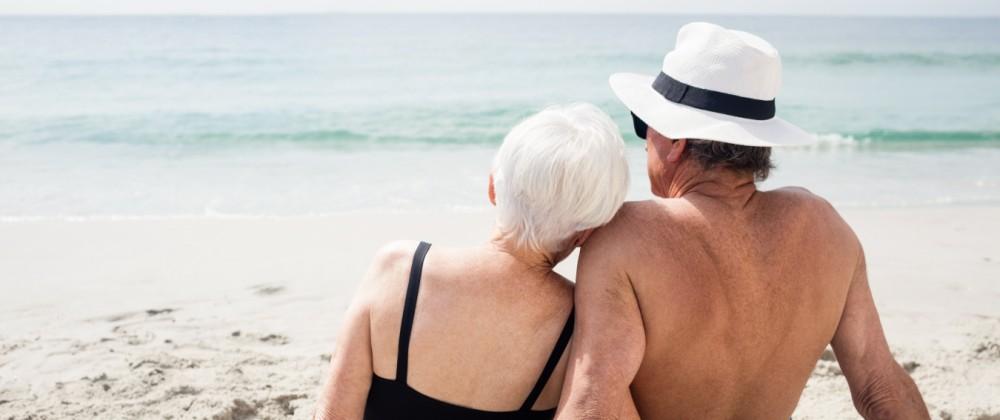 Rear view of senior couple sitting on beach