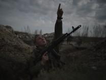 Ukraine-Konflikt: Ein Soldat zeigt in einem Schützengraben in den Himmel