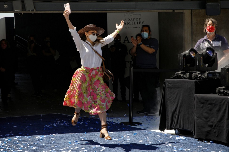 A woman leaps while arriving to greet a loved one during a mass reunion event at MetLife Stadium in East Rutherford, New Jersey