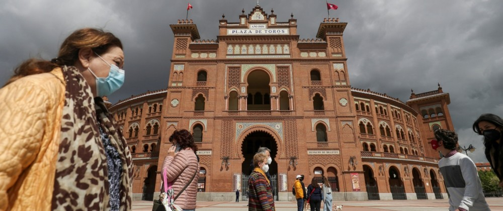 People walk past Las Ventas bullring ahead of the first bullfight since the start of the pandemic, in Madrid