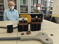 von links:  Prof. Thomas Weyh, Manuel Kuder;  hinten: herkömmliches Gerät zu Magnetstimulation, vorne ((schwarze Teile mit Aufbau)) neu entwickelte Module (ganz links das neueste)