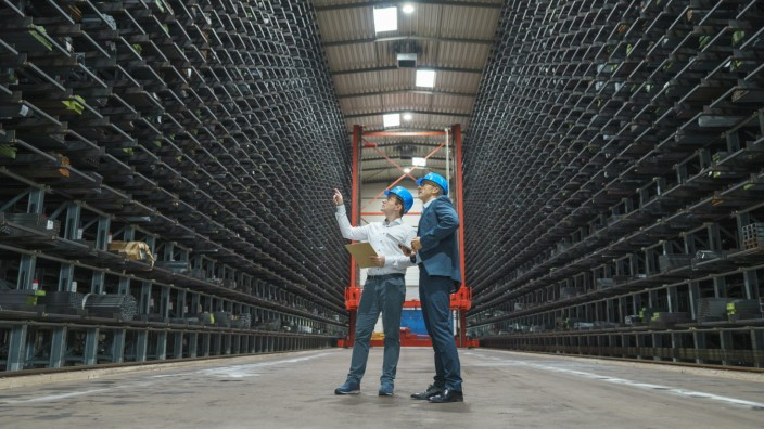 Two businessmen having a meeting in a high rack warehouse of a factory model released Symbolfoto property released MOEF0