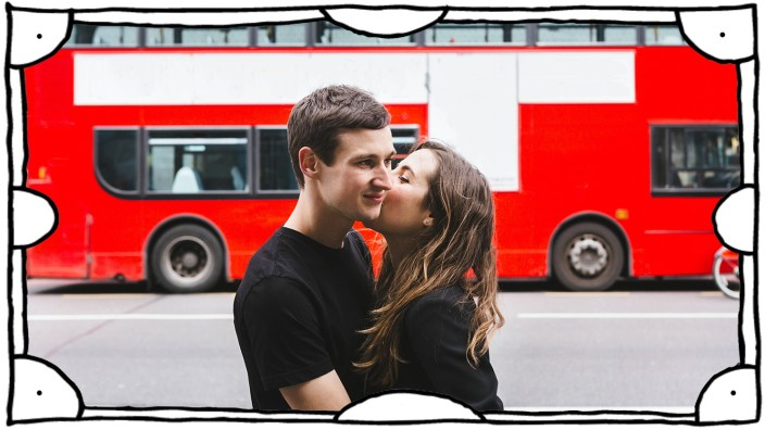 Side view of cheerful girlfriend kissing smiling boyfriend in city on background of double decker bus in London, Model r