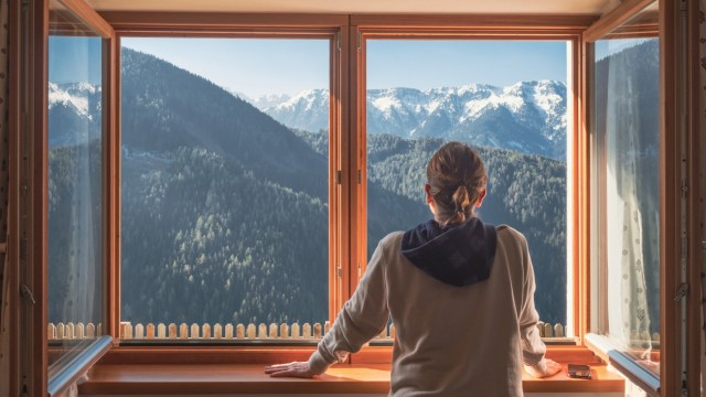 Unrecognizable female in casual outfit leaning on window sill and admiring green mountain ridge on sunny day in countrys