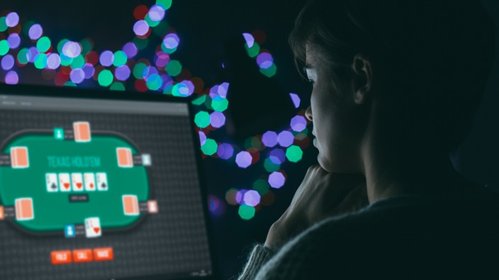 Woman playing online poker late at night, games and gambling concept (stokkete)