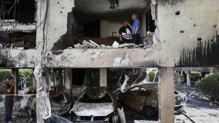 David Grossman zum Nahostkonflikt: Eine Familie im israelischen Petah Tikva inspiziert die Ruine ihres Hauses nach Raketenbeschuss aus Gaza.