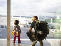 Father and daughter with backpacks at the airport looking at the planes model released Symbolfoto PU