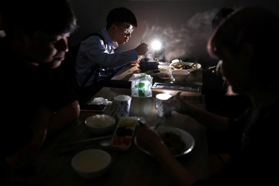 People eat using the light from their phone while experiencing a blackout due to an outage at a power plant, in Taipei