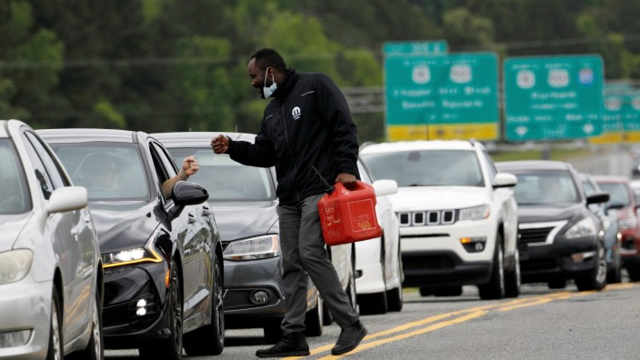 FILE PHOTO: Scores of vehicles line up to enter a gasoline station during surge in demand for fuel in Durham, North Carolina