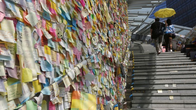 Thousands of colourful notes are displayed on 'Lennon Wall' as a couple carrying a yellow umbrella, a symbol of the Occupy Central civil disobedience movement, walks past at the Admiralty protest site in Hong Kong
