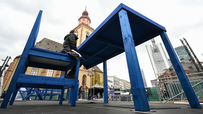Ein Riesen-Tisch und ein Riesen-Stuhl sind als Teil einer Installation vor der Frankfurter Hauptwache ein besonderes Zeichen des 3. Ökumenischen Kirchentags (ÖKT). Die gastgebenden Kirchen wollen damit zum Perspektivwechsel einladen.