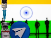 A 3D-printed Telegram app logo, small toy figurines, a syringe and vial labelled 'coronavirus disease (COVID-19) vaccine' are seen in front of India flag in this illustration