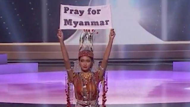 Ma Thuzar Wint Lwin, Miss Universe Myanmar, holds the 'Pray for Myanmar' sign during Miss Universe pageant's national costume show, in Hollywood