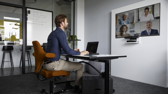 Businessman attending web conference while sitting in office model released Symbolfoto property released RBF07929