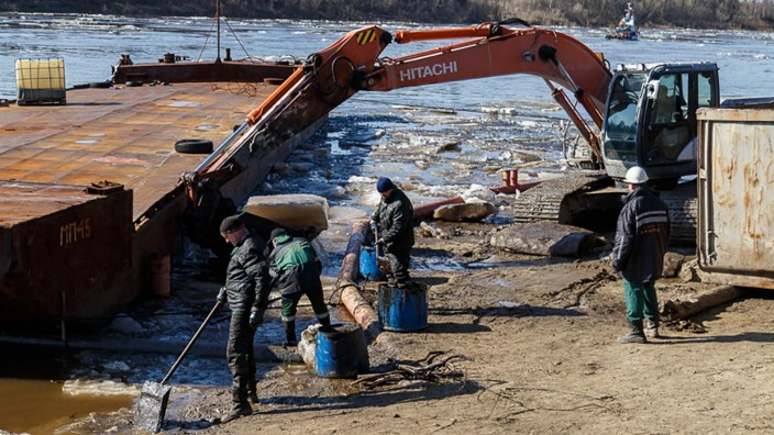 KOMI REPUBLIC, RUSSIAMAY 14, 2021: Cleaning up oil-containing fluid that got into the Kolva River in the town of Usin; KOMI REPUBLIC, RUSSIA  MAY 14, 2021: Cleaning up oil-containing fluid that got into the Kolva River in the town of Usin