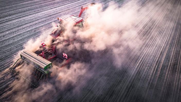 Ackerbau - Trockenheit, Traktor verschwindet bei der Aussaat von Winterraps in einer Staubwolke, Luftaufnahme. Luftaufn